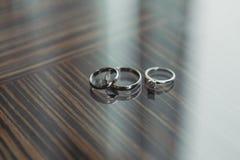 Aneis de noivado dos anéis de ouro do diamante do casamento na tabela Imagem de Stock Royalty Free