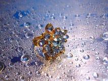 Anel azul bonito no fundo de prata com gota da água fotos de stock