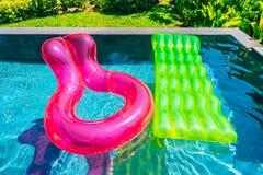 Anel colorido da nadada ou flutuador de borracha em torno da água da piscina imagem de stock