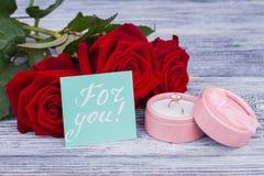 Anel da joia na caixa e em rosas vermelhas foto de stock