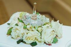 Anel de casamento Dois anéis dos noivos do vintage do ouro e um suporte de cristal com rosas brancas imagens de stock royalty free