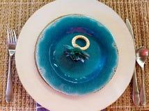 Anel de guardanapo da flor na placa azul Imagens de Stock