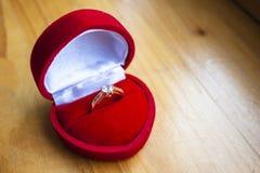Anel de noivado bonito na caixa vermelha da forma do coração foto de stock