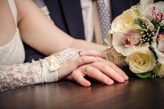Anel de ouro do casamento às mãos dos recém-casados fotos de stock