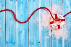 Anel de vida com corda vermelha no fundo de madeira azul Foto de Stock Royalty Free