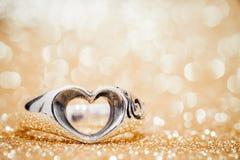Anel do coração no assoalho com bokeh dourado no fundo Fotografia de Stock