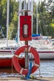 Anel do salvamento e extintor vermelhos da poeira no porto Fotografia de Stock