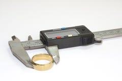 Anel dourado no compasso de calibre digital Fotos de Stock Royalty Free