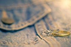 Anel falsificado do anel de diamante e de ouro colocado no jecket de Jean foto de stock