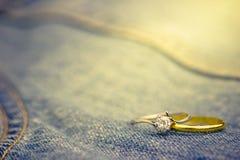 Anel falsificado do anel de diamante e de ouro colocado no jecket de Jean fotos de stock