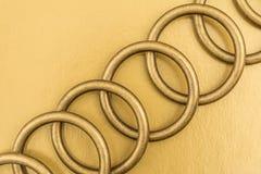 Anelli del metallo su un fondo dorato Fotografia Stock Libera da Diritti