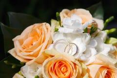 Anelli di cerimonia nuziale con i fiori immagine stock