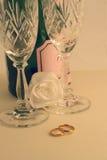 Anelli di cerimonia nuziale contro il fuoco molle di rosa, champagne Fotografie Stock Libere da Diritti