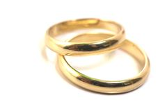 Anelli di cerimonia nuziale dell'oro isolati sopra fotografia stock