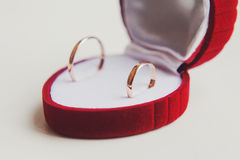 Anelli di cerimonia nuziale dorata su priorità bassa bianca monili Fotografie Stock