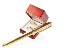 Anelli di cerimonia nuziale e penna dorata. Fotografie Stock