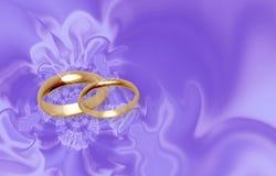 Anelli di cerimonia nuziale su materiale lilla. Fotografie Stock