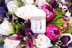 Anelli di cerimonia nuziale sui fiori Immagine Stock
