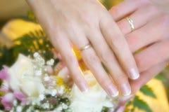 Anelli di cerimonia nuziale sull'mani Fotografia Stock