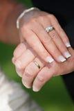 Anelli di cerimonia nuziale sulla sposa e sullo sposo Immagine Stock