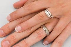 Anelli di cerimonia nuziale sulle mani Immagini Stock
