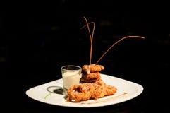 Anelli di cipolla fritti o calamari fritti su fondo scuro fotografia stock