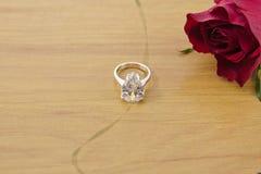 Anelli di diamante sul pavimento di legno con la decorazione di rosa Immagini Stock