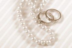 Anelli di fidanzamento d'annata di nozze e del diamante di stile di seppia retro con la collana della perla Fotografie Stock Libere da Diritti