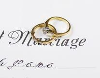 Anelli di fidanzamento del diamante e di nozze sul certificato di matrimonio Immagini Stock