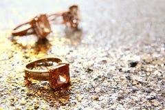 anelli di oro eleganti sul fondo di scintillio dell'argento e dell'oro Fotografia Stock