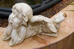 Anelli di oro di nozze e una statuetta di un angelo Immagine Stock Libera da Diritti
