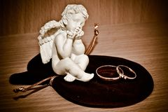 Anelli di oro di nozze e una statuetta di un angelo Immagine Stock