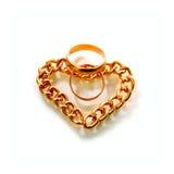 Anelli e cuore di oro dalla catena dell'oro Fotografie Stock