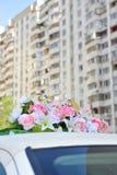 Anelli e fiori di cerimonia nuziale sul tetto dell'automobile Immagine Stock