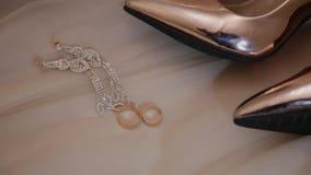 Anelli e gioielli delle scarpe delle donne dell'oro di nozze sul letto archivi video