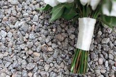 Anelli e mazzo dorati di nozze sulle pietre Fotografie Stock Libere da Diritti