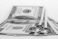 Anelli e soldi di cerimonia nuziale su una priorità bassa bianca Fotografie Stock Libere da Diritti