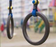 Anelli relativi alla ginnastica di legno sul campo da giuoco Fotografie Stock