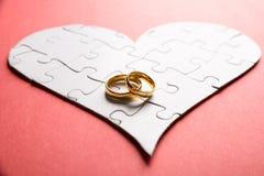 Anelli su cuore fatto del puzzle Fotografia Stock
