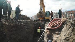 Anello concreto asssemble della botola dei lavoratori sull'escavatore in una fossa al cantiere video d archivio