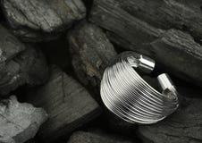 Anello d'argento dei gioielli sul fondo nero del carbone, spazio della copia Immagini Stock