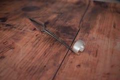 Anello d'argento tenuto dalle pinzette sul banco da lavoro immagine stock