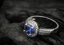 Anello dei gioielli con grande sapphir blu sul fondo nero del carbone, co Immagini Stock