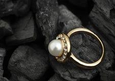 Anello dei gioielli con il diamante e perla sul fondo nero del carbone, co Fotografie Stock