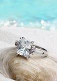 Anello dei gioielli con il diamante pulito sul fondo della spiaggia di sabbia, f morbida Fotografia Stock Libera da Diritti