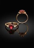 Anello dei gioielli con la gemma in forma di cuore e diamanti sul backgro nero Immagini Stock