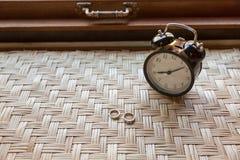 Anello delle coppie sulla tavola del tessuto con la sveglia Immagine Stock