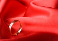 Anello di cerimonia nuziale sopra priorità bassa rossa Fotografia Stock