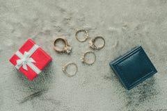 Anello di diamante dei gioielli con il contenitore di regalo sul fondo di struttura del tessuto immagine stock