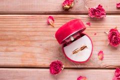 Anello di fidanzamento dorato in una scatola a forma di del cuore fotografia stock